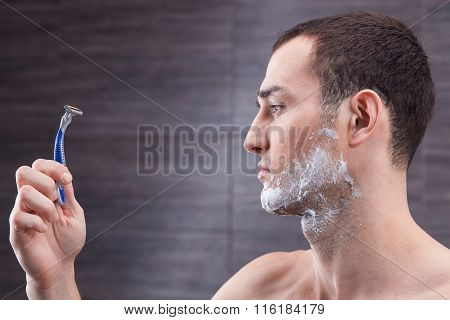 Cheerful strong guy is preparing for shaving
