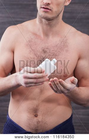 Handsome fit guy is applying moisturizer for face