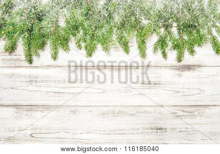Spruce Sprigs With Snow On Bright Wooden Texture. Christmas