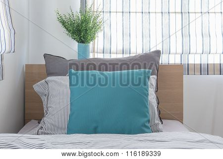 Single Wooden Bed With Pillows And Vase Of Plant