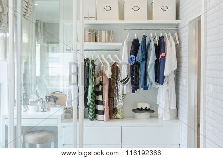 Clothes Hanging In Closet With Hat