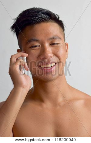 Young Asian Man chatting on his mobile phone