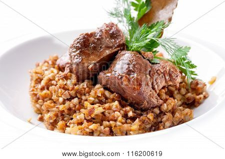 dish of buckwheat porridge with meat close-up