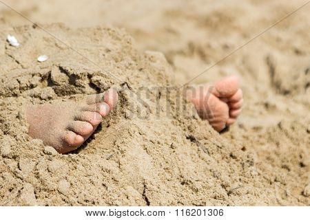 Human Feet Buried In Sand. Summer Beach.