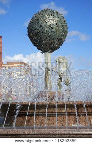 Of orange tree and a lion in the jets of water. Sculpture in the center of the fountain in the town