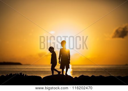 Silhouette of a two boys standing in the sun