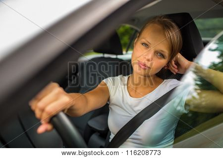 Young woman driving her car, on her way home from work - doing the daily commute