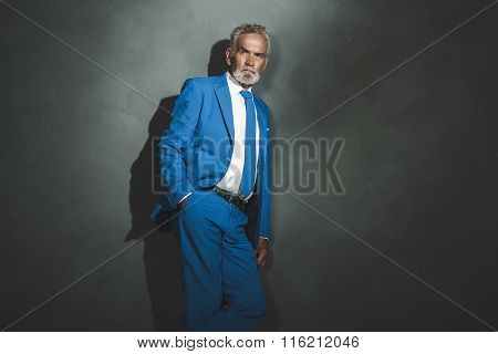 Serious Senior Businessman Leaning Against Wall