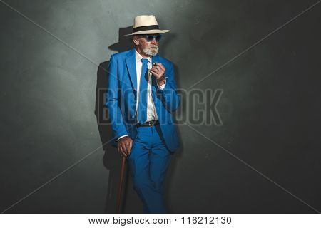 Senior Businessman With Cane Leaning Against Wall