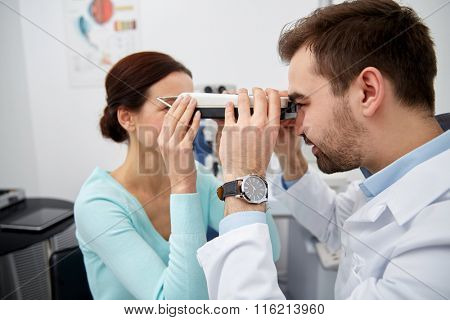 optician with pupilometer and patient at eye clinic