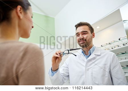 optician giving glasses to woman at optics store