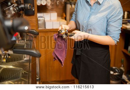 close up of woman cleaning espresso machine holder