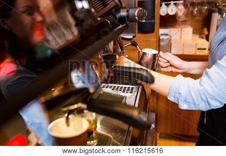 close up of woman making coffee by machine at cafe