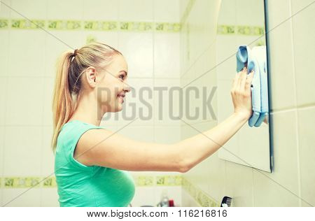 happy woman cleaning mirror with rag