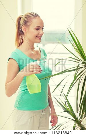 happy woman in spraying houseplants at home