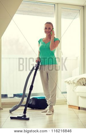 happy woman with vacuum cleaner at home