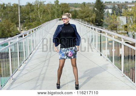 The Woman In A Miniskirt On The Middle Of The Bridge At Railway Station