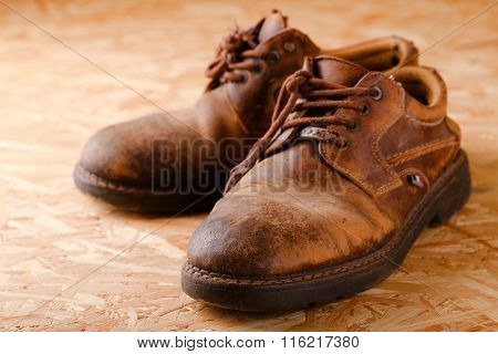 Pair Of Old Worn Shoes On Wooden Boad