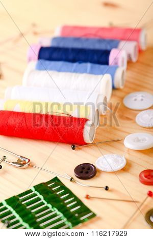 Various Threads And Other Sewing Accessories On Light Board
