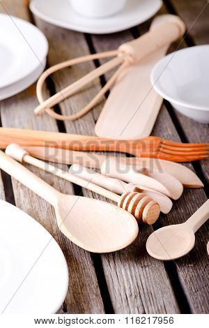 Various Wooden Spoons Among White Plates And Bowls
