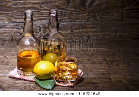 Two Bottles With A Glass Whiskey And Lemon On The Napkin