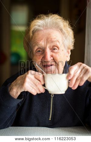 Old woman drinking tea, portrait close-up.