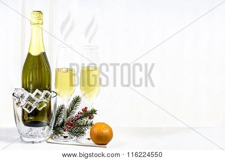 Bottle Of Champagne In Ice Bucket And Two Glasses With Mandarin And Spruce Branch Are Standing On A