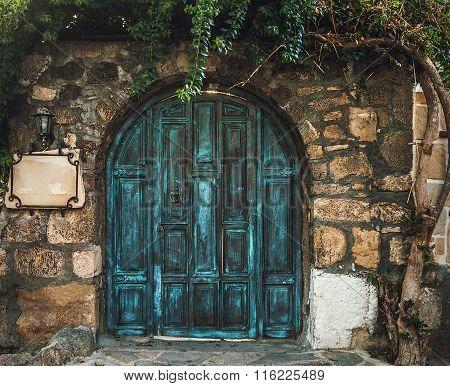 Blue Grunge Wooden Door In Brick Wall