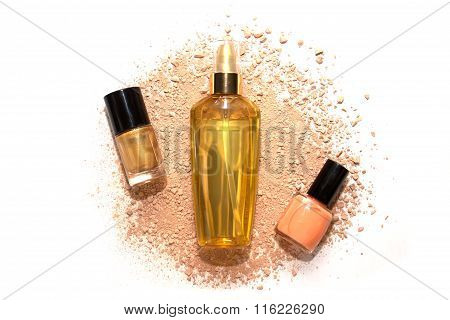 Two Nail Polishes And Hair Oil In Golden Bottle On Beige Powder