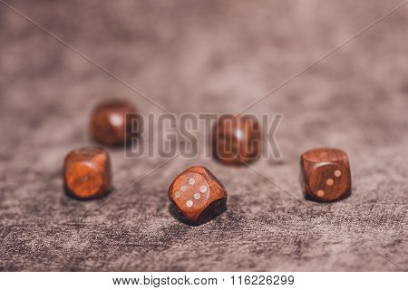 Five Wooden Dices On Brown Velvet Background