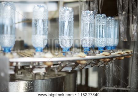 Plastic Water Bottles On Conveyor And Water Bottling Machine Industry. Water Bottling Plant.