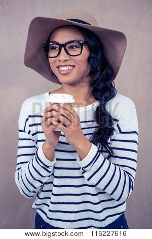 Attractive Asian woman with hat holding disposable cup and looking away