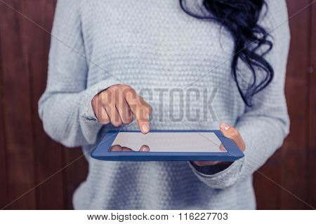 Mid section of Asian woman using tablet against wooden wall