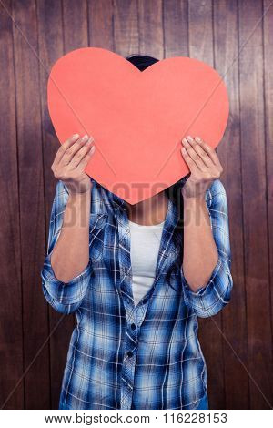Woman hiding her face behind paper heart against wooden wall