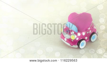 A Fun Children's Toy Car Carrying A Pink Heart Cushion. Valentine's Day Celebration Concept.