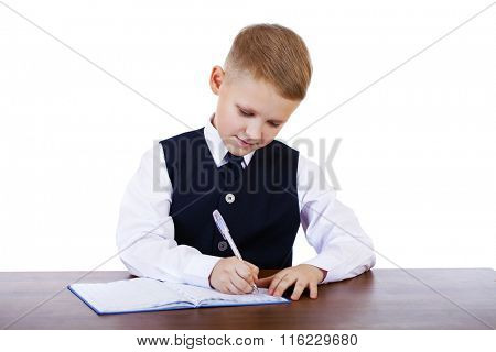 Caucasian school boy at his desk on white background with copy space - bored student boy reading book or textbook