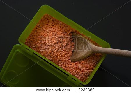 Red Lentil In Green Plastic Box On Dark Wooden Table