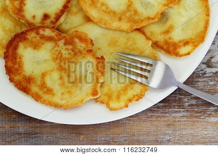 Golden potato fritters on white plate, closeup