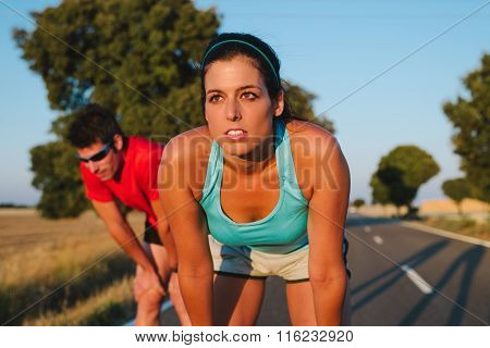 Woman And Man Resting After Running Road Race