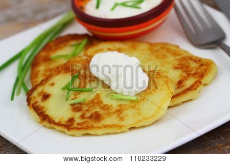 Crispy golden potato fritters with sour cream, garnished with spring onions