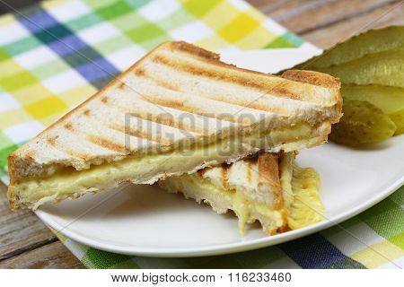 Crispy toasted cheese sandwich with gherkin on white plate