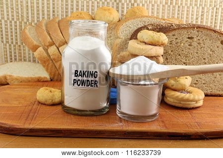 baking powder in a glass jar and wooden spoon with cookie and bread