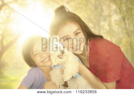 Happy Girl And Mother With Dog At The Park