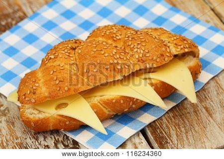 Sesame seed challah sandwich with cheese on checkered paper napkin