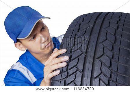 Male Mechanic Checking A Tire