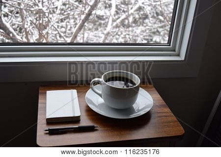 Coffee cup next to a window in winter