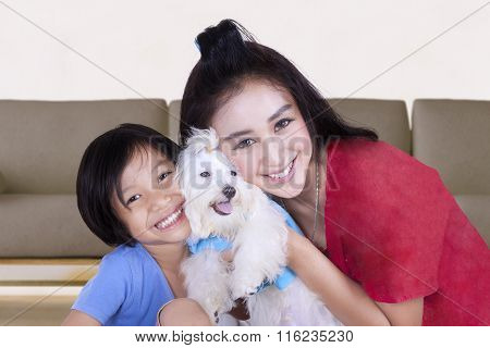 Pretty Woman And Child Holding Dog