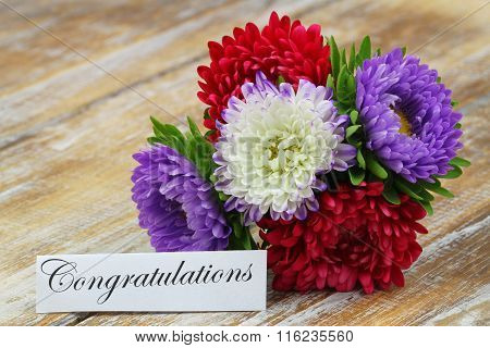 Congratulations card with colorful aster bouquet on rustic wooden surface