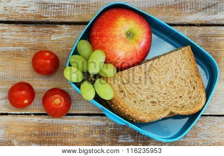 Lunch box containing brown bread sandwich, red apple, grapes and cherry tomatoes on rustic wooden su