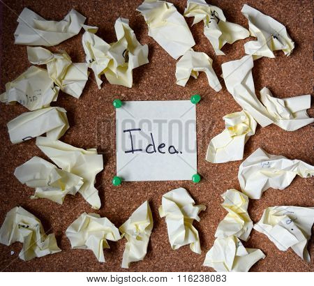 sticky note on a cork board showing an idea surrounded by failures